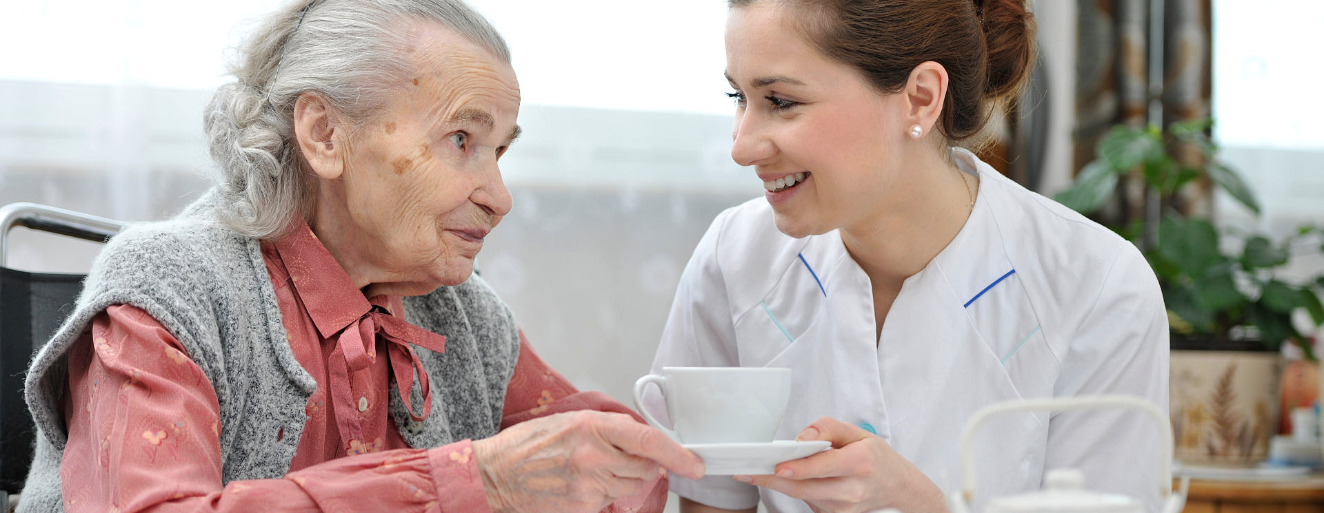 caregiver serving her patient a cup of tea