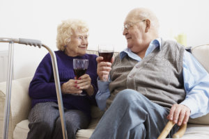 elderly couple enjoying a glass of wine together at home