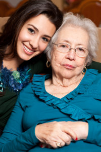 Elderly senior grandmother and teenager granddaughter in an affectionate pose in a home setting.