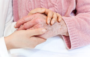 Young woman's hand holding old woman's hand
