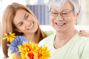 caregiver assisting her patient arranging the flower