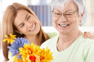 caregiver assisting her patient arranging the flower