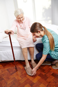 Caregiver helps dressing senior citizen women on her bed at home