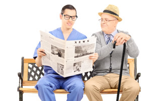 Male nurse reading a newspaper to an elderly gentleman seated on bench on white background