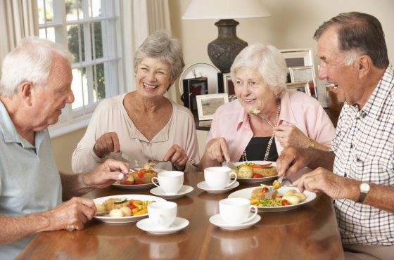 group of elderly people happily eating